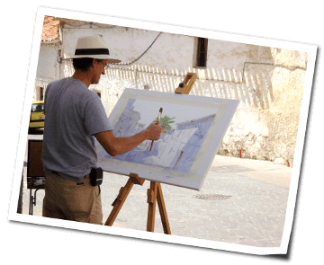Professional artist Klaus Hinkel painting in the street of the white village Frigiliana in Andalusia a street scene